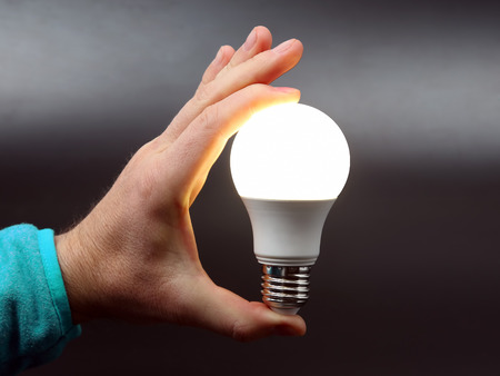 human hand holding the included led lamp on a dark background Banco de Imagens