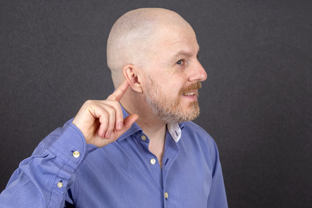 bearded man points his finger at his ear Standard-Bild