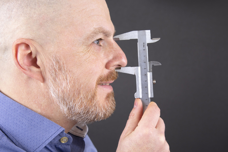 man measures the size of his nose measuring device caliper 스톡 콘텐츠
