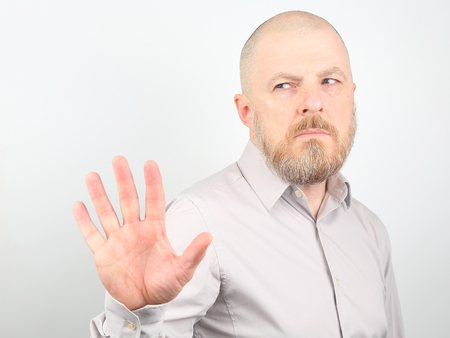 Bearded man in a shirt with a displeased facial expression and negative emotions