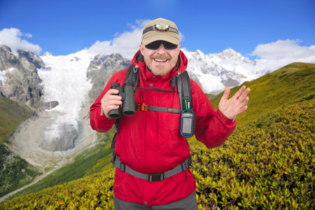 Happy man traveler with binoculars in hand on snow-capped mountains background