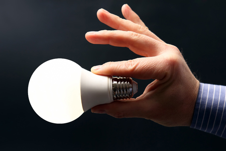 Included led new lamp in human hand on dark background. electrical industrial industry