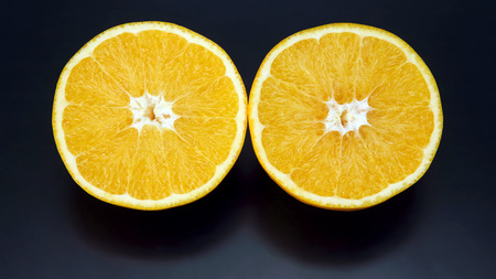 Citrus fruit. Cut orange on dark background