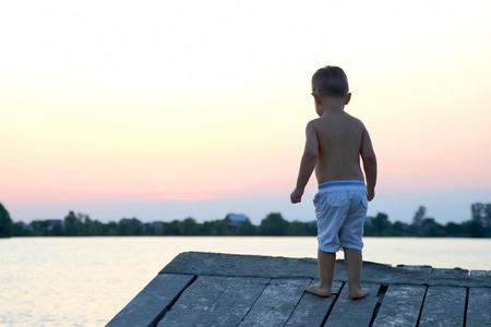 small child stands on the pier near the water