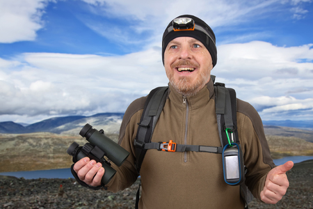 Happy man traveler with binoculars in hand on mountains background Stock Photo