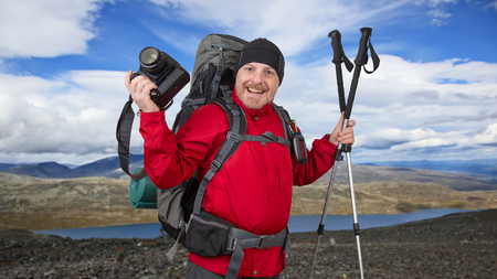 Happy bearded tourist with camera, Navigator and trekking poles on the background of beautiful mountains