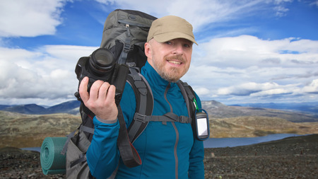 Happy bearded tourist with camera on the background of beautiful mountains