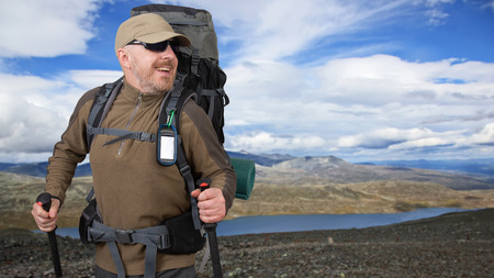 Happy male tourist with backpack is traveling in the highlands