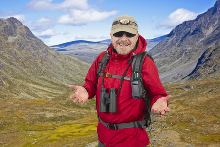 Happy man tourist with backpack is traveling in the highlands