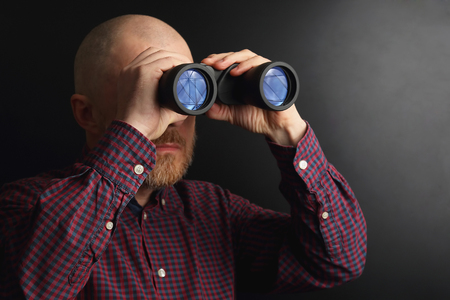 Bearded man looking through binoculars into the distance Stok Fotoğraf