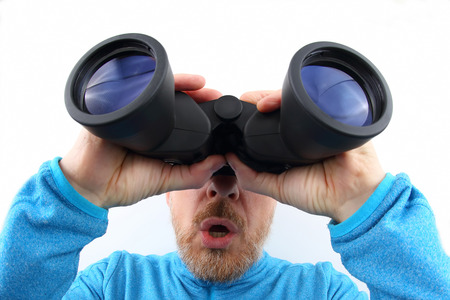 Bearded man looking through binoculars on white background