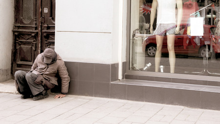 homeless man sits near the window of the store. The problem of indexation in society. Layers between poverty. Stock Photo