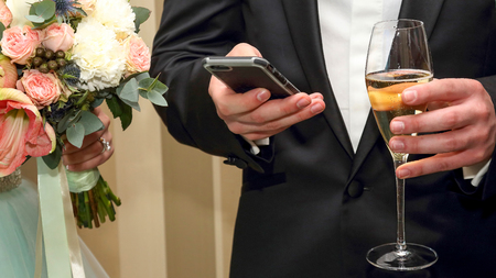 the groom with mobile and glass in hand. modern means of communication between people