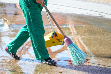 janitor cleans the sidewalk of the city from fallen leaves. maintenance of cleanliness in the city