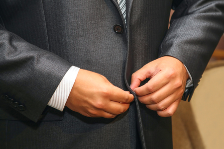 groom buttoning the buttons on the suit. Fashion and style in men's clothing Foto de archivo