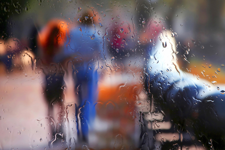 vague silhouette of two people through rainy glass. romance and family relationships in urban life 免版税图像