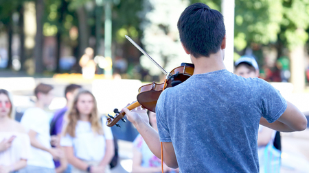 guy plays violin for street people. classical music lovers