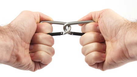 two clasped hands holding a two climbing carabiners. links and connection Banco de Imagens