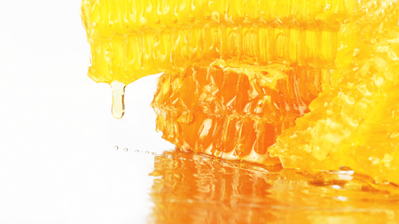 honey flowing from the honeycombs on a light background. dessert food. 免版税图像