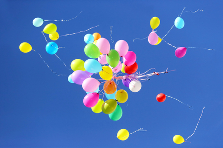 many multicolored balloons flying in the blue sky. Items to celebrate events Banco de Imagens