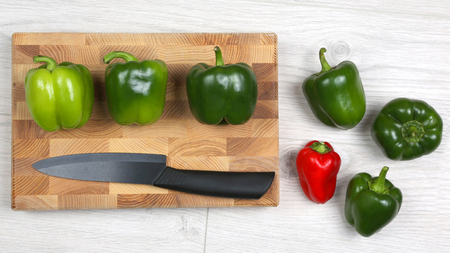 sweet peppers with a ceramic knife on a wooden board. raw food for cooking