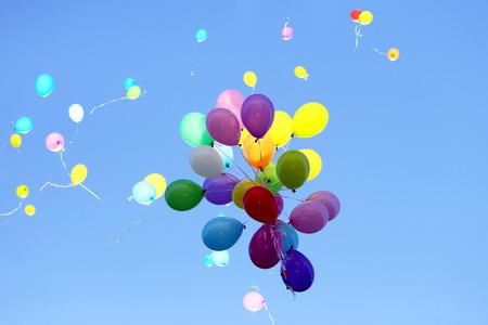 molti palloncini multicolori che volano nel cielo blu. Articoli per celebrare eventi Archivio Fotografico