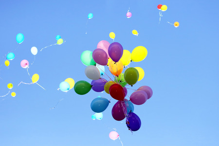 muchos globos multicolores volando en el cielo azul. Artículos para celebrar eventos Foto de archivo