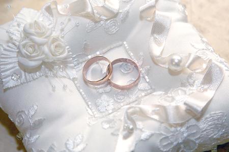 Los anillos de bodas de oro se encuentran sobre una almohada decorativa. amor y relaciones familiares Foto de archivo