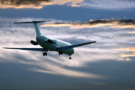 passenger jet plane flying in the evening sky at sunset. commercial airline