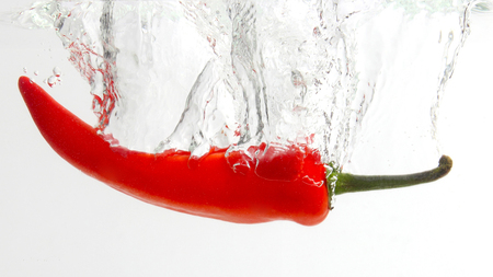red chili pepper falling in water. healthy fresh vegetables and food
