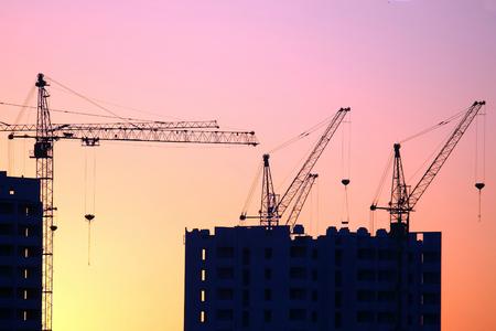 Baukräne mit gebauten Häusern auf dem Hintergrund des Sonnenuntergangshimmels. Industriebauindustrie