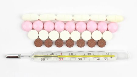 thermometer and medical pills on white background. pharmacology and medical industry Stock Photo