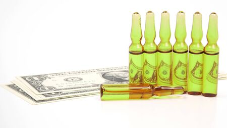 seven medical glass ampoules for injection on the background of dollar banknotes. pharmacology and medical business industry