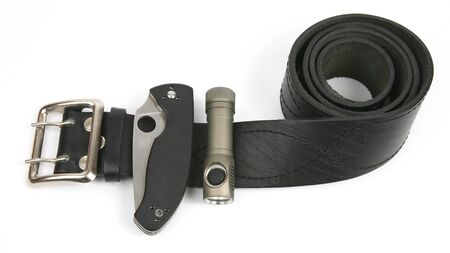 the folding knife and flashlight attached on black leather strap. everyday items 스톡 콘텐츠