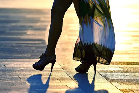 silhouette walking women legs in backlight sunlight. beauty and fashion