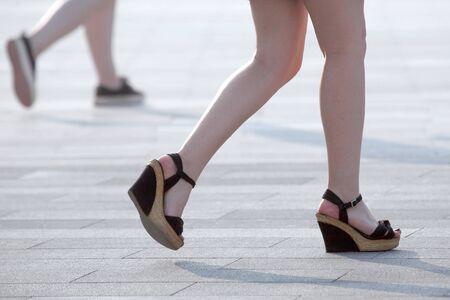 walking women legs in backlight sunlight. daily life