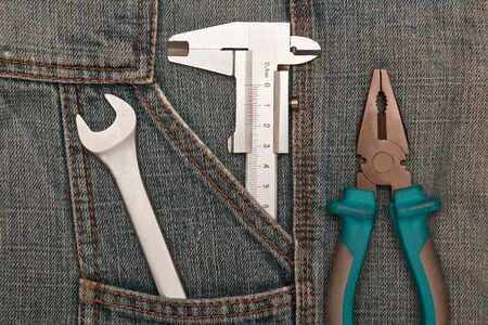 tools pliers, spanner and micrometer in jeans pocket. everyday tools Imagens