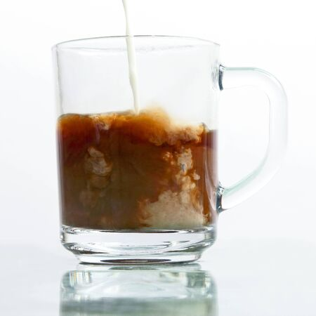 milk poured into a transparent cup of black coffee. favorite hot drink