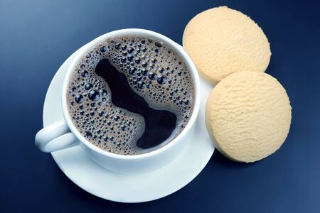 white cup of black coffee with biscuits on a dark background. hot drink