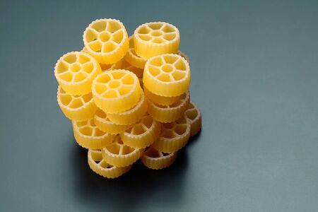 uncooked dry pasta in the shape of a wheel. raw flour food Imagens