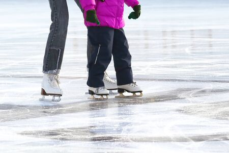 little girl with mother skate on the rink. sports, Hobbies and recreation of active people Imagens