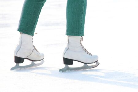 Womens feet in white ice skating on ice rink. sports, Hobbies and recreation of active people Imagens