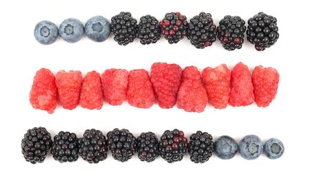 raspberries, blackberries and blueberries, located in rows on white background. healthy fresh vegetables and food