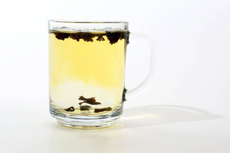 transparent cup of tea with custard on white background. hot drink