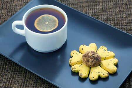 white cup of tea with lemon and biscuits. hot drink