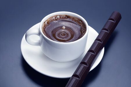 drop of milk falling in a white cup with black coffee. hot drink