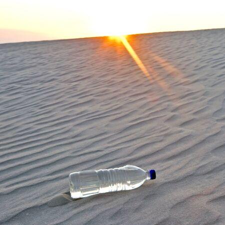 bouteille d'eau abandonnée dans le désert au coucher du soleil. soif et chaleur