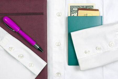 passport, money, pen, notebook and Bank cards are on a white shirt with sleeves. subjects for business and education