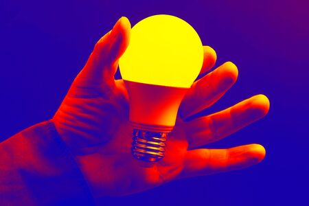 human hand holding the included led lamp on a dark background. modern electronic technologies Imagens