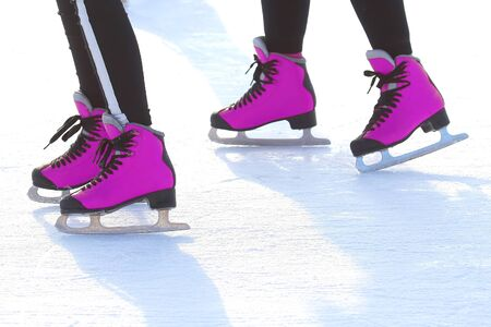 feet in pink skates on an ice rink. sports, Hobbies and recreation of active people Imagens